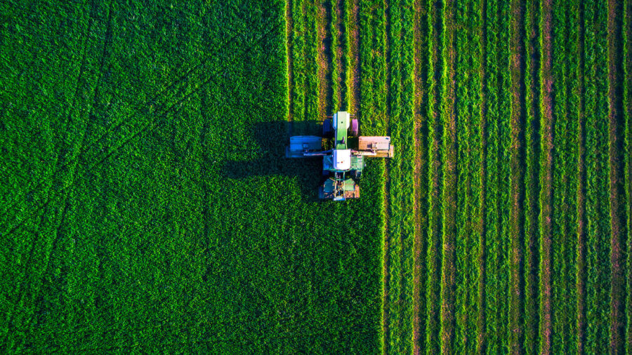 autonomous robot tractor mowing green field aerial view 499876297 900x506 1